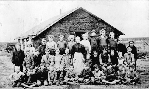 Teacher and children in front of sod schoolhouse