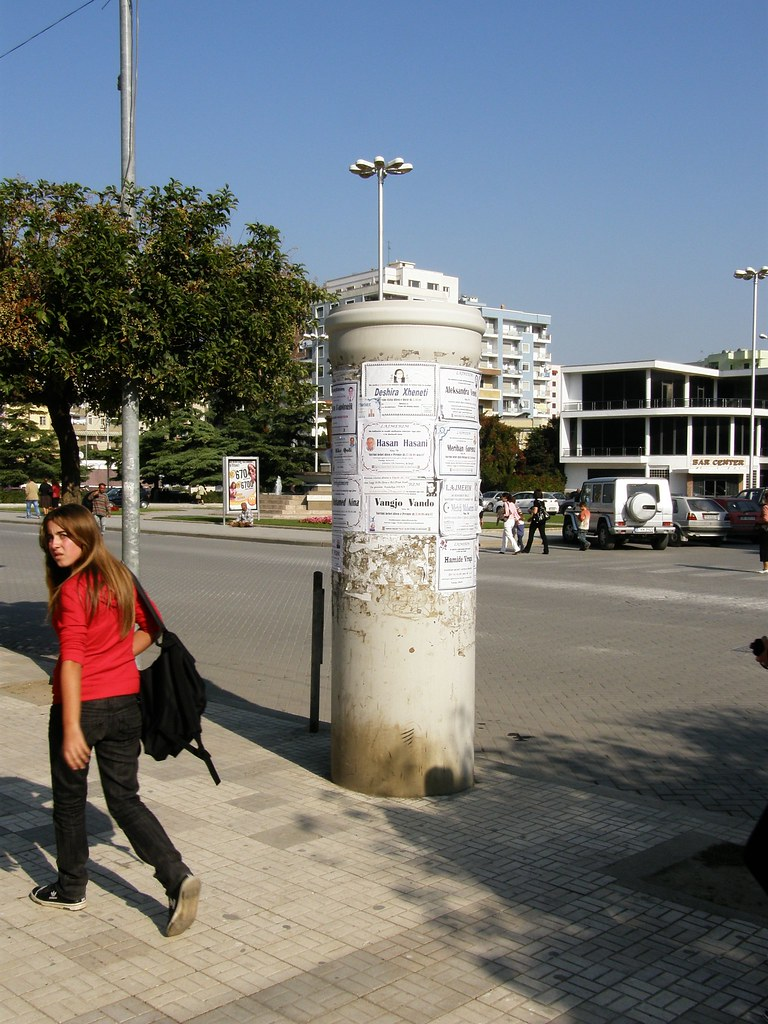 P5045 Durrës - Funeral notices on pole in front of New Mosque, and warm look from passing girl