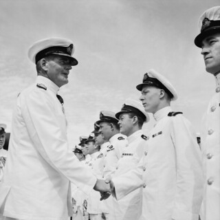 Vice Admiral Sir Guy Russell, Commander in Chief Far East Station, shakes hands with an unidentified lieutenant on board HMAS Sydney in Kure harbour, Japan.