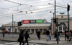 "Oxfam's ""Stop harming, Start helping"" banner at the top of Poznan central station"