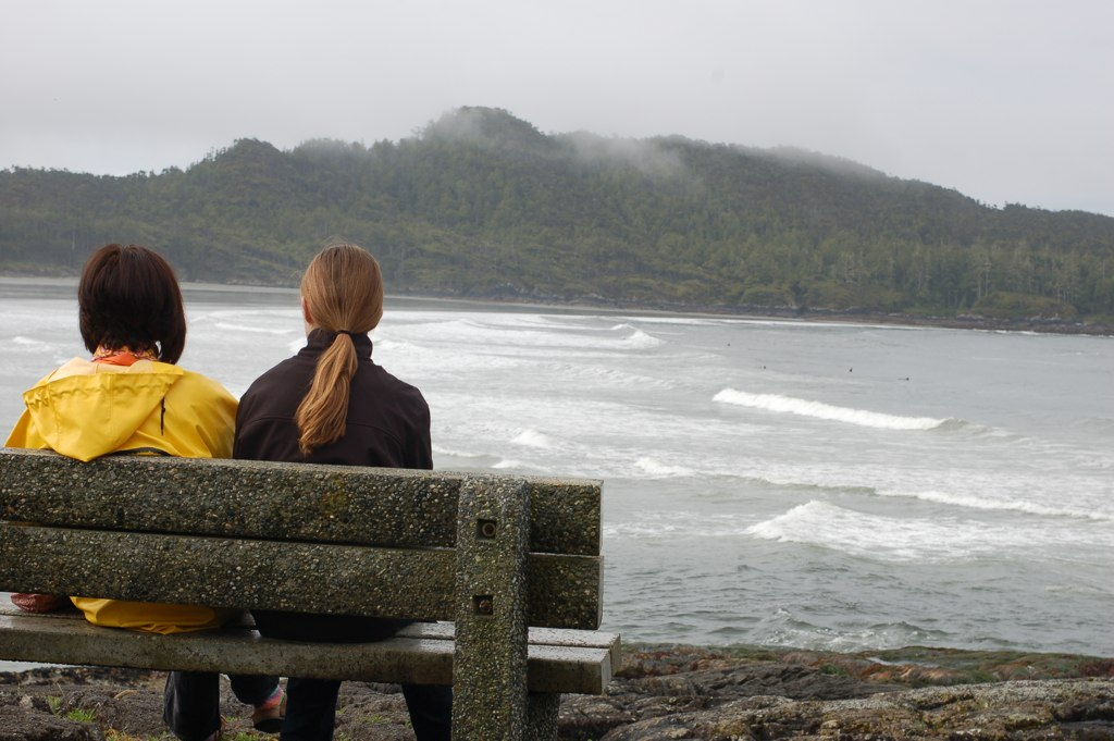 Photo of two women sitting on a bench by a bay, by Ann Voskamp.