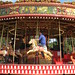 Small photo of A man rides a merry-go-round
