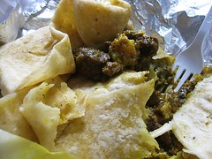 03 digging into the roti - curry goat and potatoes