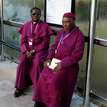 Two bishops wait to board a bus for London