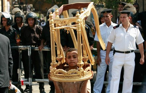 A 'young Egyptian worker' carries unfinished gold-painted wooden coffee tables  LOL