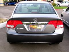 automobile(1.0), automotive exterior(1.0), wheel(1.0), vehicle(1.0), rim(1.0), honda(1.0), bumper(1.0), honda civic hybrid(1.0), sedan(1.0), land vehicle(1.0), vehicle registration plate(1.0), honda civic(1.0),