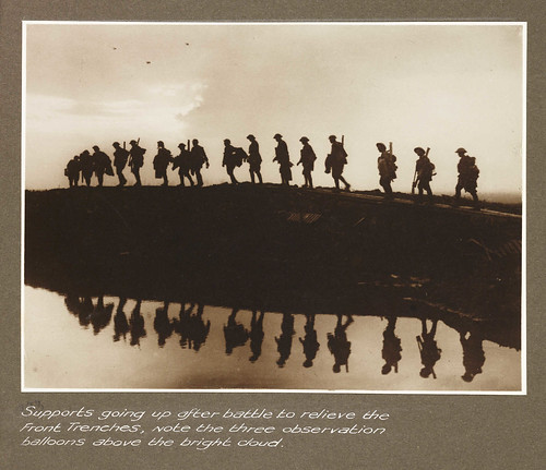 Supports going up after battle to relieve the front trenches, note the three observation balloons above the bright cloud