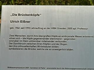 Die Brückenköpfe von Ulrich Eißner zum Bildhauersymposium Sandstein & Platte 2007 Zwei Menschen durch ihre übergroßen Köpfe an embryonale Wesen erinnernd sitzen sich, die Köpfe gegeneinander stemmend, gegenüber 361