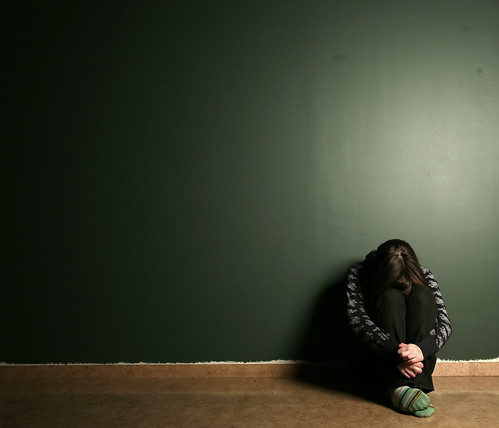 Girl crouched in fetal position in front of a dark green wall.