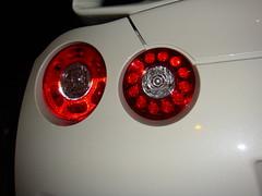 wheel(0.0), rim(0.0), headlamp(0.0), spoke(0.0), automobile(1.0), automotive tail & brake light(1.0), automotive exterior(1.0), vehicle(1.0), automotive lighting(1.0), red(1.0), automotive design(1.0), light(1.0), bumper(1.0), lighting(1.0),