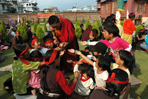 Birds of Paradise: Give Me Some Sweet Nectar too! A monk spoons out nectar, a Tibetan Buddhist Blessing for the children (and adults) outside Tharlam Monastery wearing blindfolds, Sakya Lamdre, Highest Yoga Tantra Empowerment, Bodha, Kathmandu, Nepal