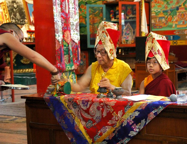 Tibetan monk gives HH Dagchen Rinpoche more rice for visualizing offerings as he rings a ghanta (bell) with HE Asanga Sakya