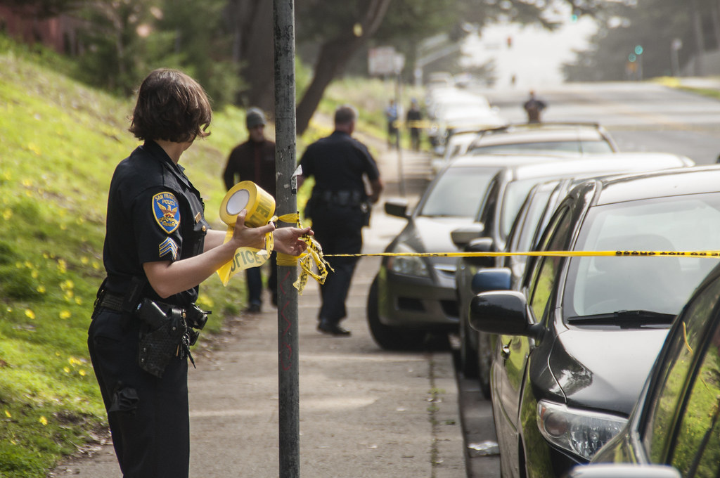 A police officer tapes off a perimeter after a driver blacked out, clipped a parked car and crashed on Lake Merced Boulevard between Font Boulevard and Higuera Street around 2:30 p.m. Thursday, March 6. Photo by Jessica Christian / Xpress