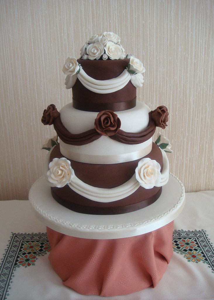 Chocolate and ivory wedding cake with roses & swags / drapes