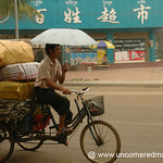 Man Cycling with an Umbrella - Xishuangbanna, China
