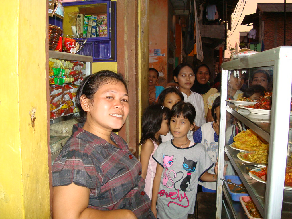 Five dollars a Day by BBC World Service, on Flickr CC Rokiyah makes five dollars a day by selling food in the Kampung Pulo neighbourhood in Jakarta. She laughs at the idea of going to one of the expensive shopping malls in the center of the city.