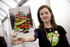 "An Oxfam activist showing a ""Stop Harming - Start Helping"" Christmas card delivered to UN Climate negotiators in Poznan"