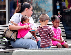 woman with three children on park bench