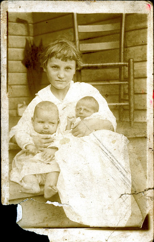 Young girl holding two babies