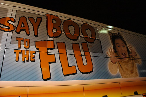 Say BOO to the FLU, sign on the side of a bus, little girl in costume, San Francisco, California, USA by Wonderlane