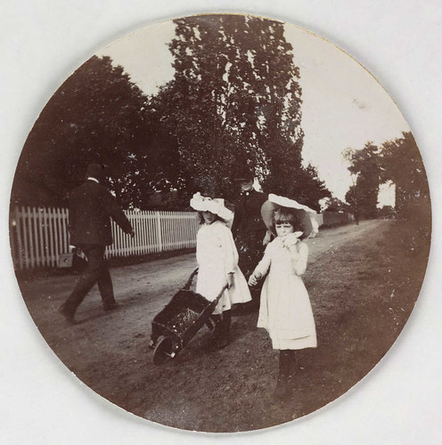 Children walking with a wheelbarrow