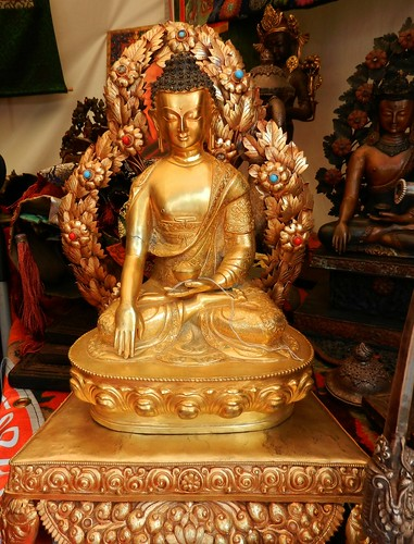 Ornate brass statue of Lord Buddha in the earth touching mudra surrounded by leaves, webbed fingers, lotus and wish fulfilling jewels ornaments, another similar statue behind, Tibetan goods for sale, tent, Kalachakra for World Peace, Washington D.C., USA by Wonderlane