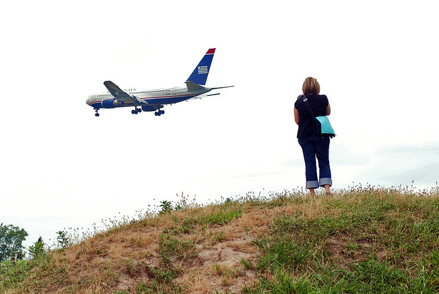 She stood on a hill looking at the passing airliner...