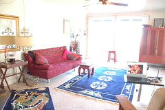 After global warming, Tibetan style living room, red sofa, red Chinese chairs, blue Tibetan carpets, photo of Dilgo Khyentse Rinpoche on laptop, chest, San Mateo, California, USA