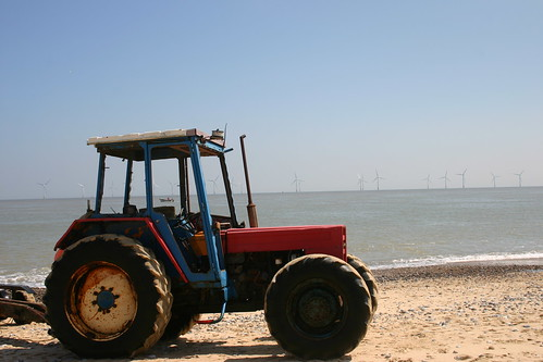 The tractor, the fishing  boat and the wind farm. A Norfolk beach.