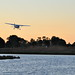 Small photo of Airplane landing over the water near dusk