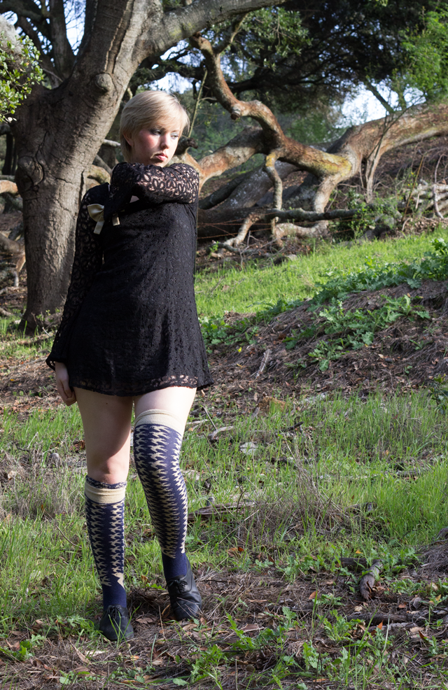 black lace mini dress with bell sleeves, gold bow brooch, knee socks with bird pattern