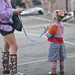 Young girl on a leash  holds beer for mommy while mommy sends text to her boyfriend, Satan.