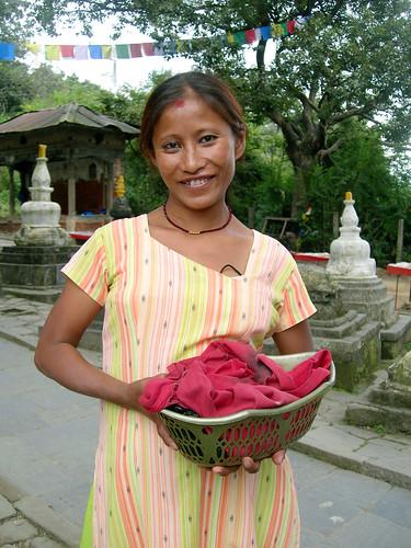 Lovely girl holding a basket, on the way to Swayambhunath Stupa, prayer flags, chorten, Kathmandu, Nepal - photo by Steve D. by Wonderlane