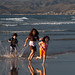 Three Children romp in the chilly water at Morro Bay