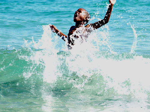 A child shouts for joy in a wave at the beach
