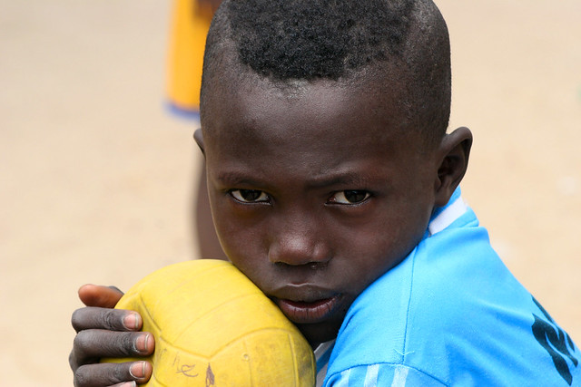 A portrait of a boy with a soccer ball.