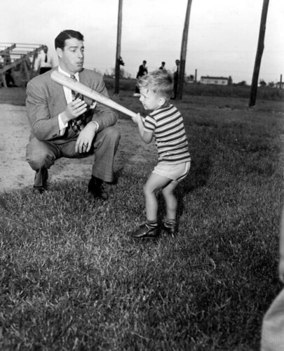 Joe DiMaggio showing three year old Larry Valencourt how to hold a batWest Palm Beach,  Florida