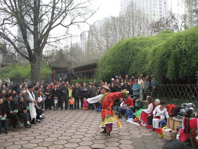 A performer in the People's Park attracts a crowd of onlookers
