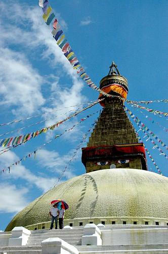 Boudha Stupa, with two friends under an multi-colored umbrella, Tibetan Buddhist prayer flags, Boudha, Kathmandu, Nepal by Wonderlane