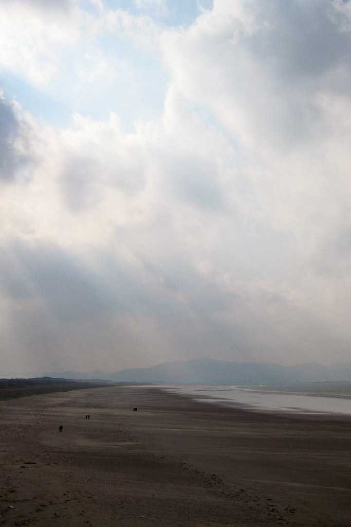 Rays of sunlight penetrate thick clouds along the beach in Ireland.
