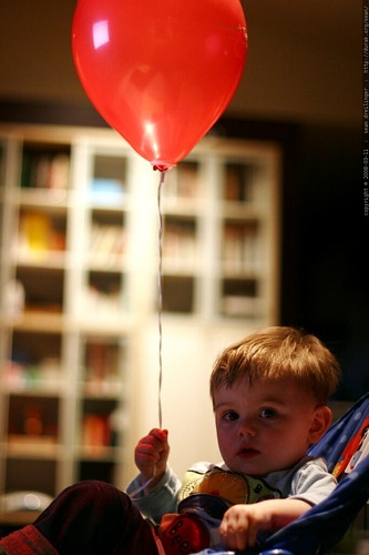in his chair, watching his baby movie, holding his balloon    MG 0447