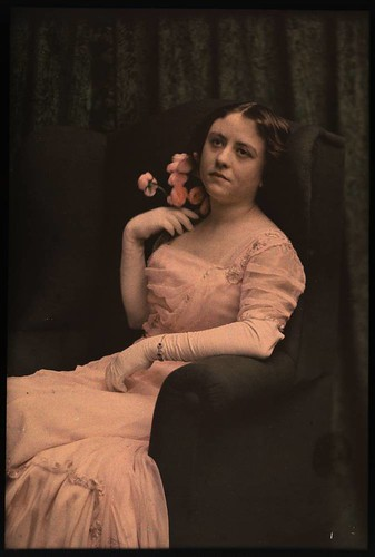 Woman in pink dress sitting in chair holding roses