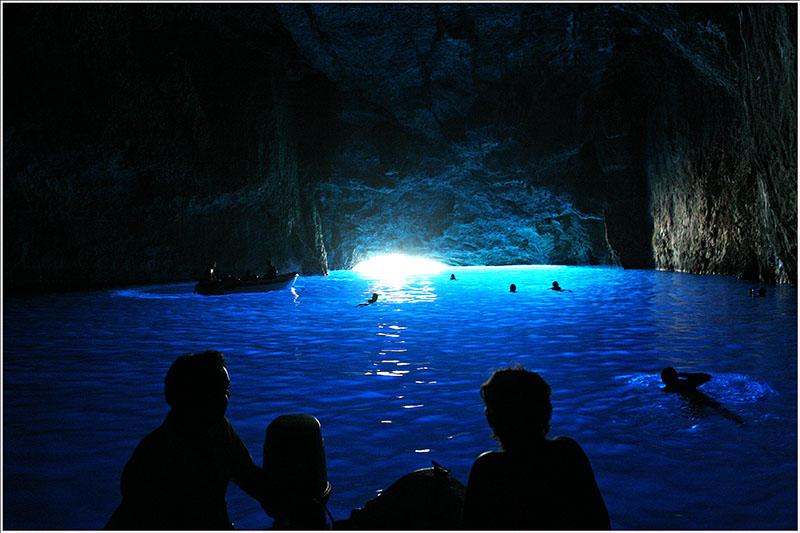 ザキントス島の青の洞窟の内部で泳ぐ人々