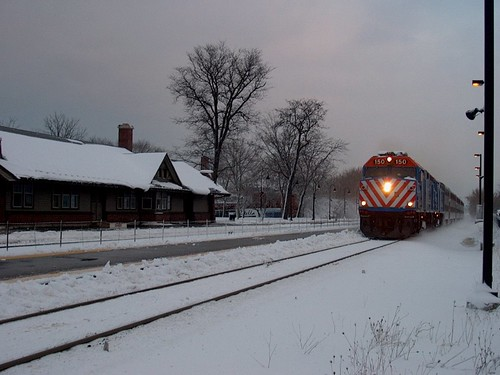 Westbound Metra express commuter train passing the Norwood Park. Metra commuter rail station. Chicago Illinois. Friday, December 1st, 2006 Chicago snowstorm. by Eddie from Chicago