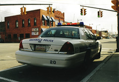 taxi(0.0), compact car(0.0), person(0.0), automobile(1.0), automotive exterior(1.0), law enforcement(1.0), ford crown victoria police interceptor(1.0), vehicle(1.0), police(1.0), police car(1.0), full-size car(1.0), sedan(1.0), ford crown victoria(1.0), luxury vehicle(1.0), vehicle registration plate(1.0), motor vehicle(1.0),