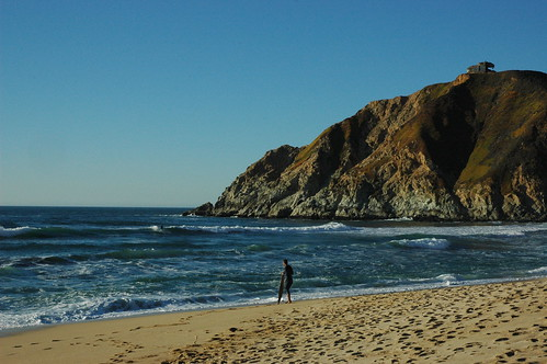 Surfers in those last few waves before sunset, clear winter day, blue sky, hill, Gray Whale Cove beach, old World War II bunker, Pacific Coast, near San Francisco, California, USA by Wonderlane
