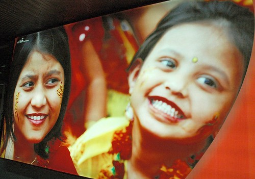 Henna painted on two smiling girls, red, photo advertisment promoting tourism, airport, Dhaka, Bangladesh by Wonderlane