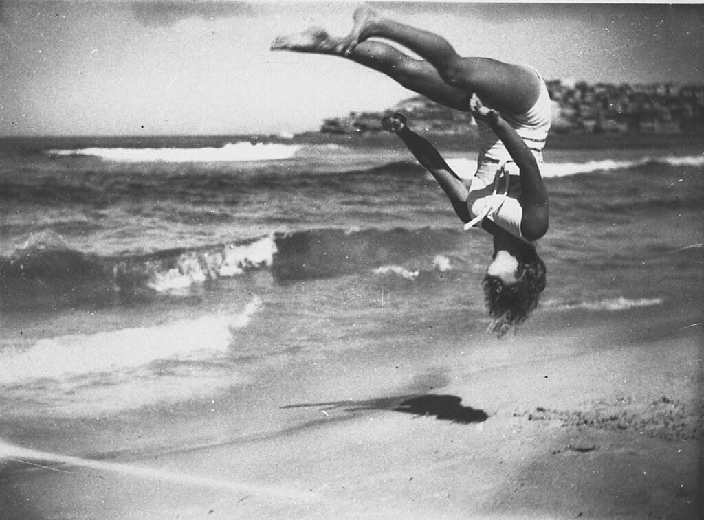 Peggy Bacon in mid-air backflip, Bondi Beach, Sydney, 6/2/1937 / by Ted Hood