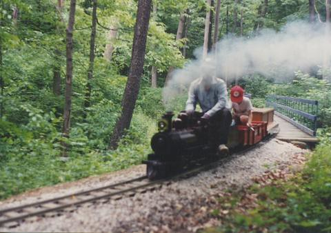 "7 and 1/2 "" guage steam train rounding a curve in the woods. The Hesston Steam Museum. Hesston Indiana USA. June 1994. by Eddie from Chicago"