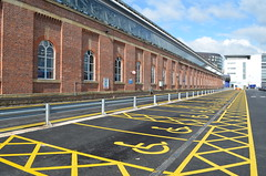 Plenty of disabled parking at Manchester Piccadilly Station with this view of the brickwork that's along platform 1 of the station, the roof is supported by this wall and rows of cast iron columns, round-headed windows can been seen spaced between each column....